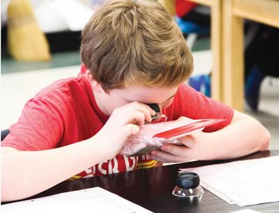 Boy studies insulation materials with loupe.