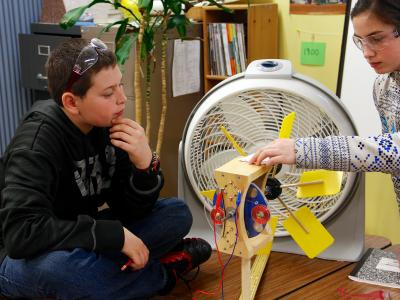 Girl and boy work on model turbine