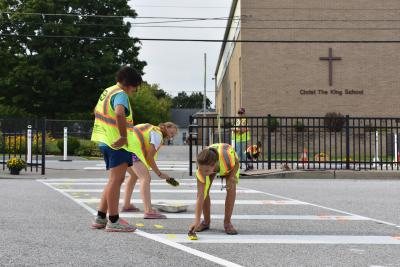 Students painting the crosswalk in front of Christ the King School.
