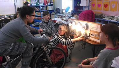 Student pedals the energy bike while VEEP educator Laura explains light board