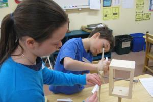 Young girl and young boy adjust dowels on a model windmill