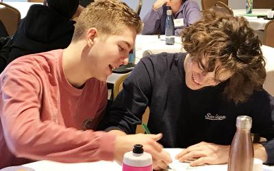 two teen boys working on a document together